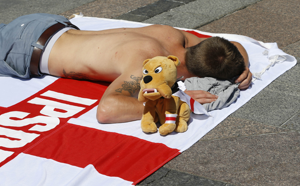An England fan from Ipswich sleeps next to his 'British Bulldog'. (AP Photo/Kirsty Wigglesworth)