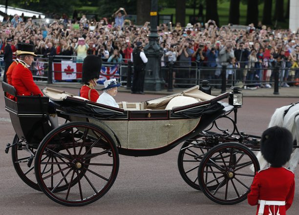 "Britain's Queen Elizabeth II, accompanied by Prince Philip, leaves in a horse-drawn carriage to attend the Trooping the Colour parade, in central London, Saturday, June 14, 2014. Queen Elizabeth II is celebrating her birthday with traditional pomp and circumstance. More than 1,000 soldiers, horses and musicians are taking part in the parade known as ""Trooping the Color,"" an annual ceremony.(AP Photo/Lefteris Pitarakis)"