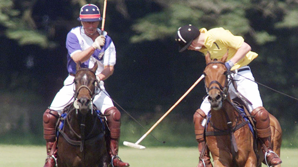 Prince Harry, right, competes with his father the Prince of Wales on the polo field at Cirencester Park Polo Club, Gloucestershire, Sunday June 24 2001. His brother Prince William and Australian model Elle MacPherson were among the crowd watching the match. (AP Photo/Chris Ison, PA)