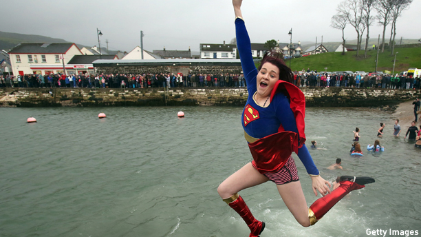 A woman in a fancy dress costume jumps into Carnlough harbour, north of Belfast in Northern Ireland on January 1, 2015 for the annual New Years day charity harbour plunge. AFP PHOTO / PAUL FAITH        (Photo credit should read PAUL FAITH/AFP/Getty Images)