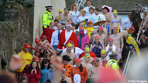SOUTH QUEENSFERRY, SCOTLAND - JANUARY 01: Revelers make their way down steps as they joined around a thousand New Year swimmers, many in costume, braved freezing conditions in the River Forth in front of the Forth Rail Bridge during the annual Loony Dook Swim on January 1, 2013 in South Queensferry, Scotland. Thousands of people gathered last night to see in the New Year at Hogmanay celebrations in towns and cities across Scotland..  (Photo by Jeff J Mitchell/Getty Images)