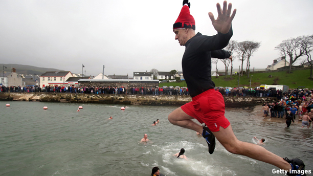 A man jumps into Carnlough harbour, north of Belfast in Northern Ireland on January 1, 2015 for the annual New Years day charity harbour plunge. AFP PHOTO / PAUL FAITH        (Photo credit should read PAUL FAITH/AFP/Getty Images)