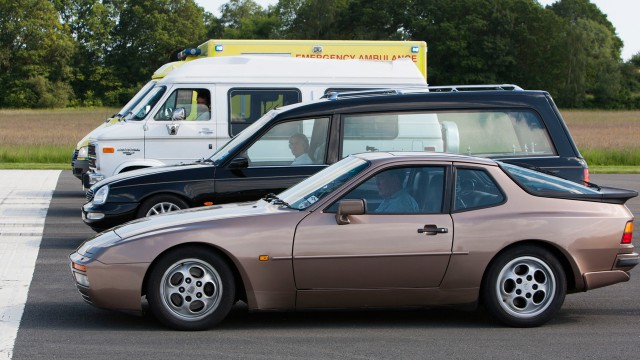 An NHS ambulance, the Chevrolet GMC Day Van V8, the Ford Scorpio Cardinal Hearse and the Porsche 944 Turbo