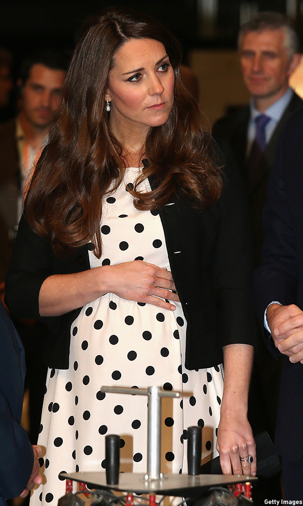 "Catherine, Duchess of Cambridge cradles her ""Baby bump"" as she looks at exhibits during a visit at the Warner Brother's studio in Leavesden on April 26, 2013. AFP PHOTO/POOL/CHRIS JACKSON        (Photo credit should read Chris Jackson/AFP/Getty Images)"