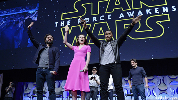 "ANAHEIM, CA - APRIL 16: Cast members (L -R) Oscar Isaac, Daisy Ridley, John Boyega of ""Star Wars: The Force Awakens"" and back row (L-R) writer, director and producer J.J. Abrams, producer Kathleen Kennedy and host Anthony Breznican, Entertainment Weekly reporter, acknowledge fans at the kick-off event during Disney's Star Wars Celebration 2015 at the Anaheim Convention Center April 16, 2015. The Star Wars Celebration runs through April 19. (Photo by Kevork Djansezian/Getty Images)"