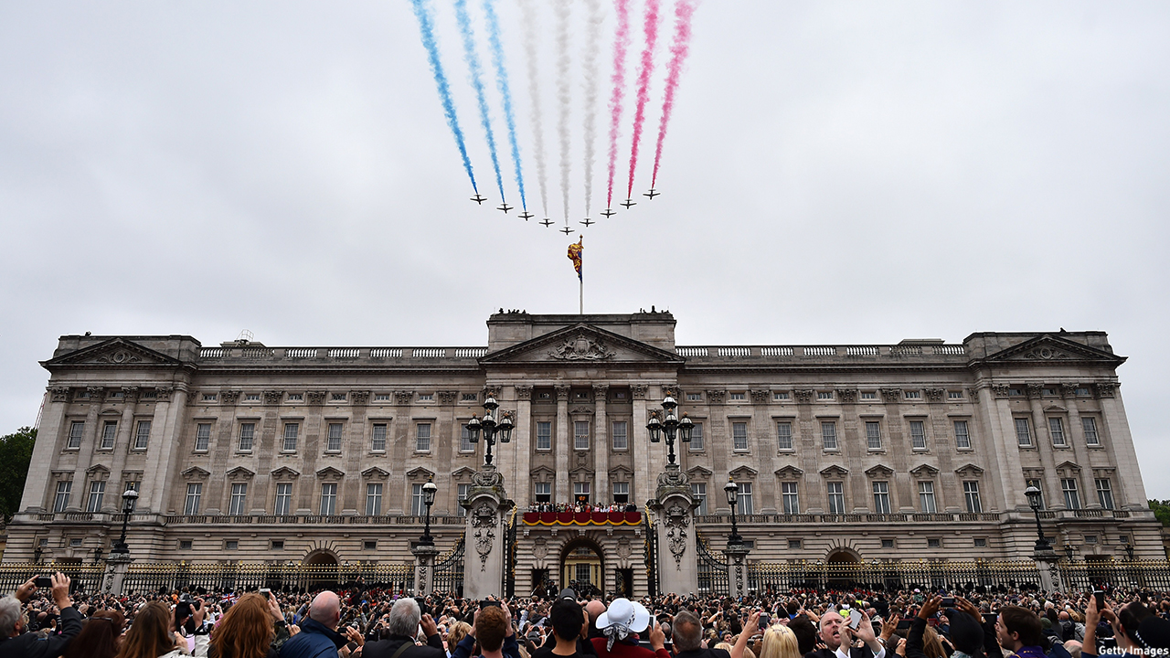 Spectators watch the Royal Air Force Aerobatic Team, the Red Arrows, perform a flypast at the end of the Queen's birthday celebration. (BEN STANSALL/AFP/Getty Images)