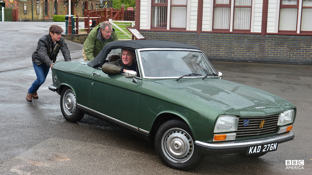 Richard Hammond and Jeremy Clarkson pushing James May in a Peugeot 304 Cabriolet.