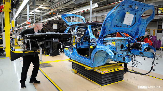 A cockpit being fitted to a blue car.