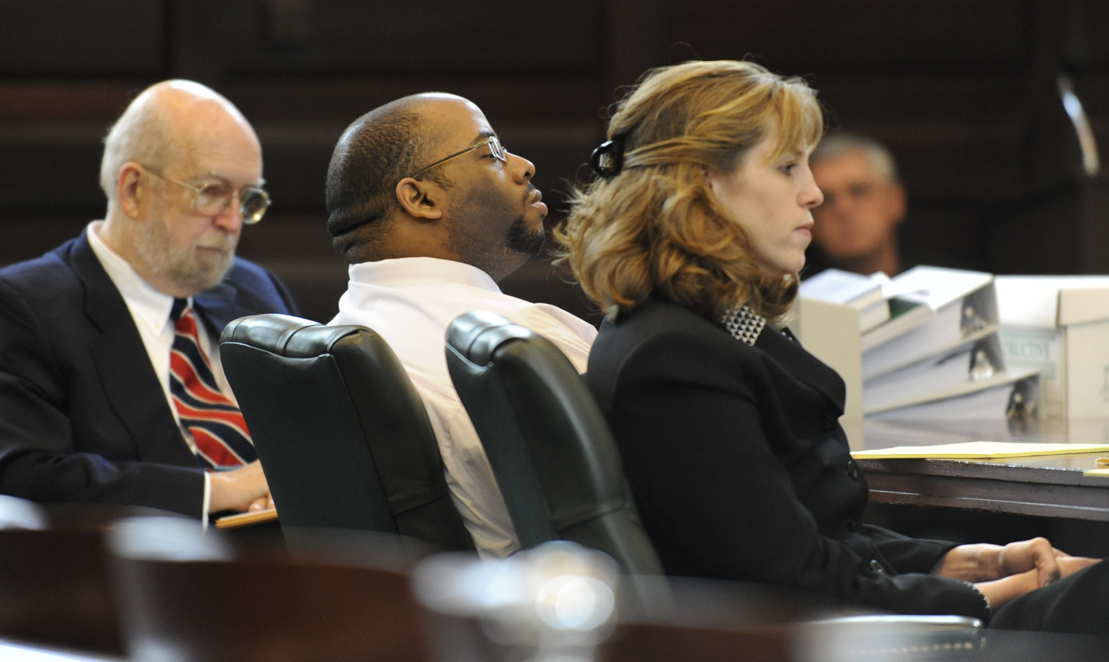 "Still for the documentary ""Scenes of a Crime""; Murder defendant Adrian Thomas(c) listens to the opening statements flanked by his defense attorneys Jerome Frost(l) and Ingrid Effman(r) in Rensselaer County Courthouse in Troy, New York October 2, 2009."