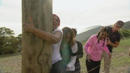 Traci tries to get her big booty through the strings with the help of her sisters.