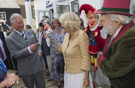 Royal visit to kent. The Prince of Wales and the Duchess of Cornwall with Des Turner the Punch and Judy man at the Whitstable Oyster Festival in Kent. Picture date: Monday July 29, 2013. The Prince of Wales and the Duchess of Cornwall were visiting Whitstable, and Chatham Dockyard as part of a tour of Kent. See PA story ROYAL Charles. Photo credit should read: Arthur Edwards/The Sun/PA Wire URN:17184186 (Press Association via AP Images)
