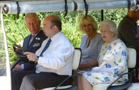 Prince Charles, Camilla Duchess of Cornwall, and Queen Elizabeth II arrive in a golf buggy to tour part of the Coronation Festival yesterday in the Buckingham Palace garden. (Photo via AP)