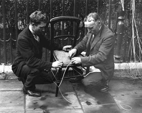 1928, Two caners fixing a chair.