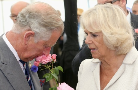 Royal visit to the Sandringham Flower Show. The Prince of Wales and the Duchess of Cornwall smell roses at the 132nd Sandringham Flower Show at Sandringham House in Norfolk. Picture date: Wednesday July 31, 2013. See PA story ROYAL Charles. Photo credit should read: Chris Jackson/PA Wire URN:17202206 (Press Association via AP Images)