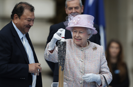Queen Elizabeth II places her message in the baton to travel the Commonwealth. (AP)