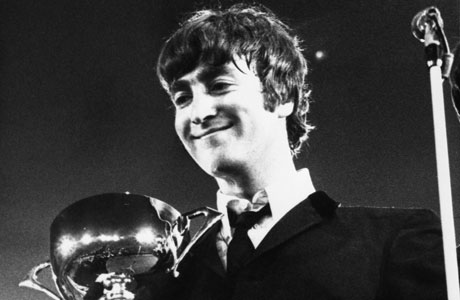 John Lennon holds an NME award, 1964. (AP Images)