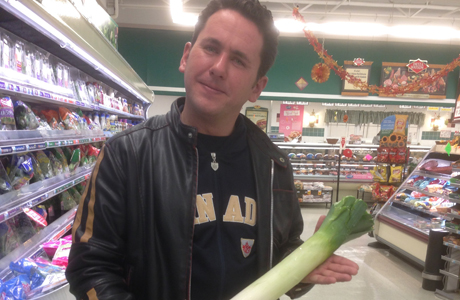 David Perry shops for fresh produce, holding a leek. (Molly Horan)