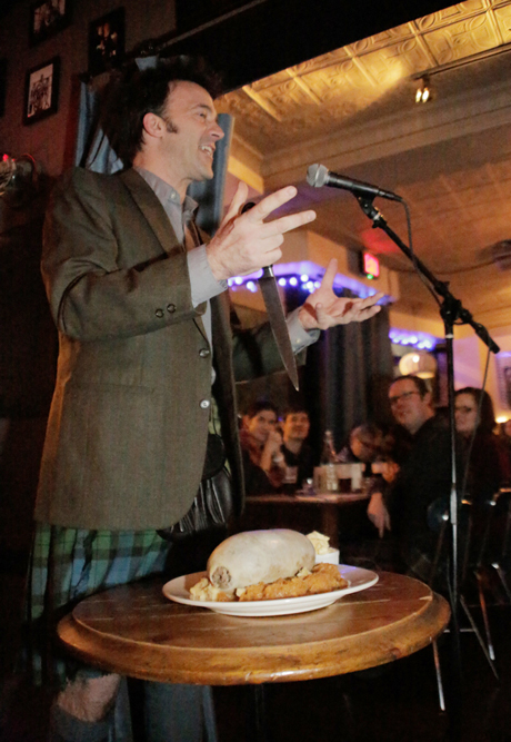 "Jason Waddleton addresses the Haggis at The Haven in Jamaica Plain, MA. The Haven hosts six Burns Suppers over four nights; and sells approximately 100 Haggis ""takeaway"" for people to host their own suppers. (Sarah Ganzhom)"