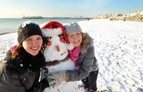 Winter weather.Lecky (left) and Lucy (right) cuddle their snowman on the snow covered beach in Brighton. Picture date: Friday December 18, 2009. Heavy snow brought travel chaos to Britain today, with flights cancelled, roads closed, motorists stranded in their cars and rail services disrupted. See PA story WEATHER Snow. Photo credit should read: John Stillwell/PA Wire URN:8144624