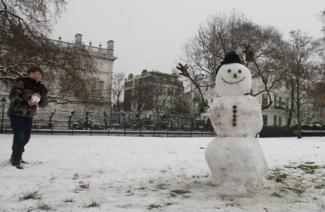 A boy makes a snowman in Green Park in London, Sunday, Feb. 5, 2012. Snowfall and freezing weather conditions across the country are causing disruption to transport, with ice across much of Britain. (AP Photo/Kirsty Wigglesworth)