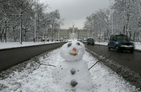 A snowman is seen in the middle of The Mall as traffic passes by, London, Monday, Feb. 2, 2009. Heavy snowfall in much of Britain caused widespread travel problems throughout the country Monday morning, causing hundreds of flight cancellations and rush hour chaos in London. In the background is Buckingham Palace. (AP Photo/Alastair Grant)