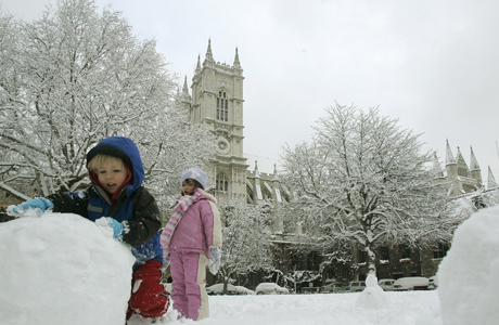 Robbie aged 2 1/2 and is sister Clara roll a snow ball as they make a snowman near Westminster Abbey, in background, in London, Monday, Feb. 2, 2009. Britain's capital ground to a halt on Monday after an overnight snowstorm _ the worst in 18 years _ blanketed the city and caused hundreds of flight cancellations and nightmare commutes.(AP Photo/Alastair Grant)