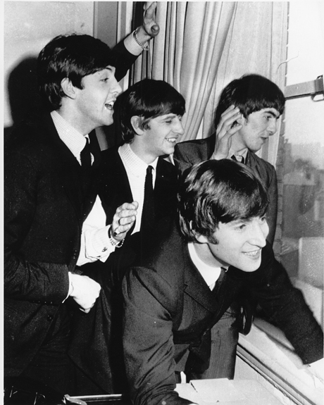 The Beatles wave to fans assembled below their Plaza Hotel window after they arrived in New York City on Feb. 7, 1964 for a short tour of the United States. From left to right are, Paul McCartney, Ringo Starr, John Lennon, and George Harrison. (AP Photo)