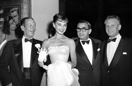 "Young actress Audrey Hepburn attends the opening of her first motion picture ""Roman Holiday"" with a star-studded escort; seen from left are: songwriter Cole Porter, composer Irving Berlin and producer Don Hartman, on September 19, 1953, in Hollywood, California. (AP Photo)"