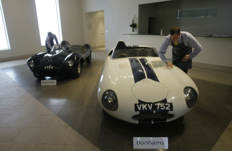 Bonhams employees pose for photographs beside the very first production Jaguar D-Type to roll off the production line in 1955, left, and a prototype Jaguar 'E2A' during a photocall at the auction house's offices in London, Thursday, July 3, 2008.  The E2A is expected to fetch in excess of US$7 million (4.44 million euro) in the Bonhams and Butterfields annual Quail Lodge sale in California on August 15 and the D-Type between 2,000,000 and 2,500,000 pounds sterling (US$3.97 million to 4.96 million, 2.52 million to 3.14 million euro) in Bonhams' Goodwood Festival of Speed sale on July 11.  (AP Photo/Matt Dunham)