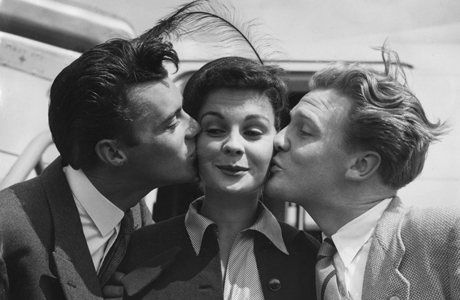 British actress Jean Simmons, 20, is delighted as she is kissed by actors Dirk Bogarde, left, and Donald Houston at London's Northolt airport, England, July 8, 1949 on her way to visit Germany, Austria and Switzerland. (AP Photo)