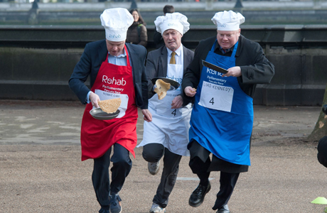 Journalist Robbie Gibb (L), David Amess MP (C) and Lord Kennedy (R) Rehab Parliamentary Pancake Race in Victoria Tower Gardens, Westminster, London, Britain - 04 Mar 2014 The charity race is organised as a competition between journalists, MPs and members of the House of Lords and proceeds are given to the charity 'Rehab'.  (Rex Features via AP Images)