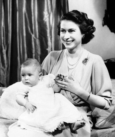 Prince Charles of Edinburgh, left, takes the proceedings seriously as he and his smiling Mother, Princess Elizabeth, pose for first informal pictures in Buckingham Palace, April 10, 1949, London, England. (AP Photo)