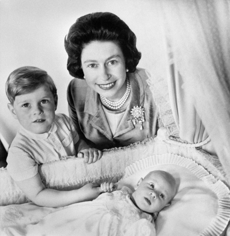 Prince Edward, fourth child of the Queen and the Duke of Edinburgh, grips the finger of his brother, four year old Prince Andrew, as the Queen bends over the baby's crib in the Music Room of Buckingham Palace. (Press Association via AP Images)
