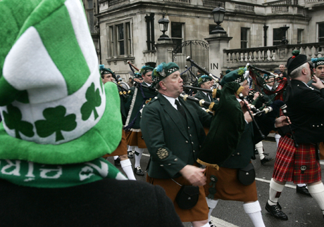 A spectator watches band members play bagpipes as they parade through central London during the St Patrick's Day celebration, Sunday, March 16, 2008. (AP Photo/Sang Tan)
