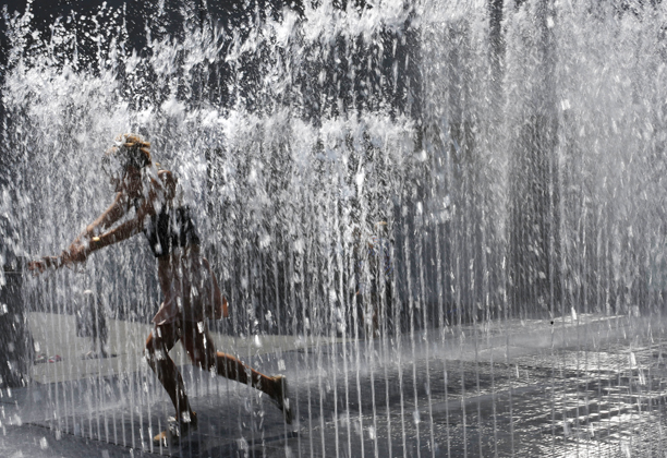 A woman runs through a fountain at the Southbank in London, Thursday, July 18, 2013. Britain continues to bask in hot weather Thursday with temperatures in London peaking at 26 Celcius/79 Fahrenheit. (AP Photo/Sang Tan)