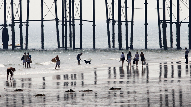 People enjoy the beach in Hastings, England, Thursday, July 2, 2009. Parts of England continued to maintain hot and humid conditions until Friday as the Met Office raised its heatwave alert level in parts of England. (AP Photo/Sang Tan)