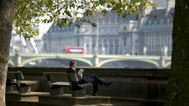 A man reads a book as a bus passes over Westminster Bridge with the former County Hall in the background in London, Wednesday, May 23, 2012.  Britain's met office has forecast temperatures of 27 degrees Celsius (80 Fahrenheit) in London Wednesday, making it the hottest day the capital has experienced so far this year.  (AP Photo/Matt Dunham)