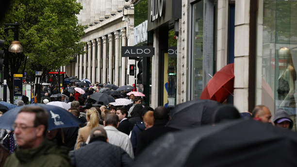 Shoppers shelter from the rain under umbrellas as they walk along Oxford Street in London, Wednesday, April 25, 2012.  Britain's economy has fallen back into recession for the first time since 2009 after official figures Wednesday showed that it unexpectedly contracted during the first three months of the year.  The Office for National Statistics said economic output as measured by gross domestic product fell by 0.2 percent in the first three months of the year from the previous quarter. The first quarter drop follows the 0.3 percent decline recorded in the last quarter of 2011 and means Britain has returned to recession as two consecutive quarters of negative growth are required for a country to be officially deemed to be in recession.  (AP Photo/Matt Dunham)