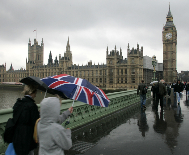 A pedestrian holding an umbrella featuring a Union flag walks across Westminster Bridge back-dropped by the Houses of Parliament in London, Wednesday, April 7, 2010. Britain is bracing for a May 6 general election that may alter the landscape of its politics _ a race that offers at least three unpredictable outcomes and one of the most dramatic since Tony Blair defeated the Conservatives in 1997. (AP Photo/Akira Suemori)
