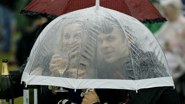 Spectators shelter under an umbrella as rain stops play at the All England Lawn Tennis Championships at Wimbledon, Tuesday, June 28, 2011. (AP Photo/Kirsty Wigglesworth)