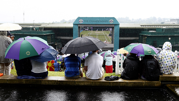 Tennis - 2011 Wimbledon Championships - Day Eight - The All England Lawn Tennis and Croquet Club. Spectators shelter from the rain under umbrellas at the top of Murray Mount URN:11071551