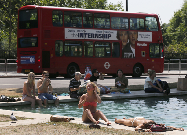 People enjoy the sun near a fountain at Hyde Park in London, Monday, July 8, 2013. England's capital experienced the warmest days of the year with temperatures up to 29 Celsius (84 Fahrenheit). (AP Photo/Frank Augstein)