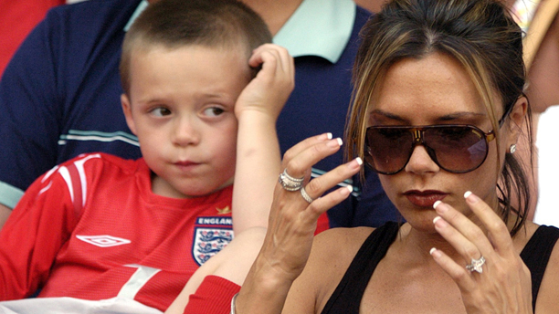 (dpa) - Victoria Beckham (L), wife of English midfielder David Beckham, and their son Brooklyn smile as they follow the Soccer Euro 2004 group game opposing England and Switzerland at the Cidade Stadium in Coimbra, Portugal, 17 June 2004. England won 3-0.  +++NO MOBILE PHONE APPLICATIONS+++ Photo by: Bernd Weissbrod/picture-alliance/dpa/AP Images