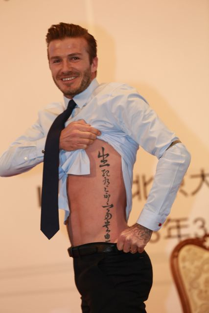 English soccer superstar David Beckham, shows his tattoos of Chinese characters during an exchange meeting at Peking University in Beijing, China, 24 March 2013. David Beckham arrived in Beijing on Wednesday (20 March 2013) morning to start his China tour as the image ambassador of the Chinese Super League.(Imaginechina via AP Images)