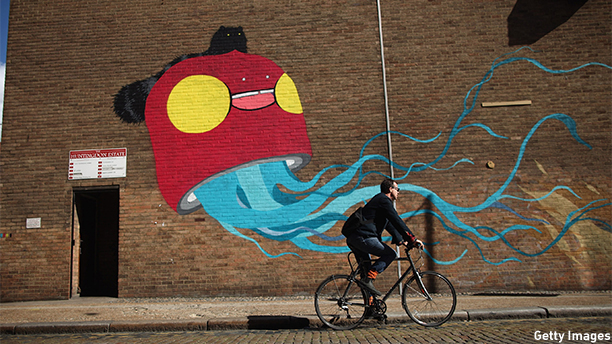 LONDON, ENGLAND - SEPTEMBER 18:  A man cycles past a large piece of street art near Brick Lane on September 18, 2012 in London, England.  (Photo by Dan Kitwood/Getty Images)