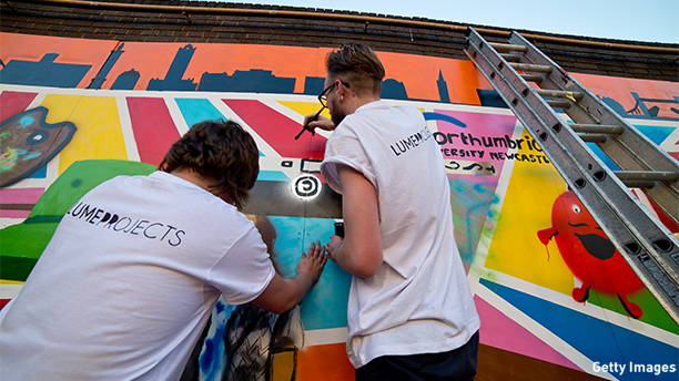 LONDON, ENGLAND - JULY 03: Craig Mathew and Andrew Potts add the finished touches to their work. A guerilla street art mural that brings Northumbria University, Newcastle's student designs to life at Ely's Yard on July 3, 2014 in London, England.  (Photo by Ben A. Pruchnie/Getty Images for Northumbria University)