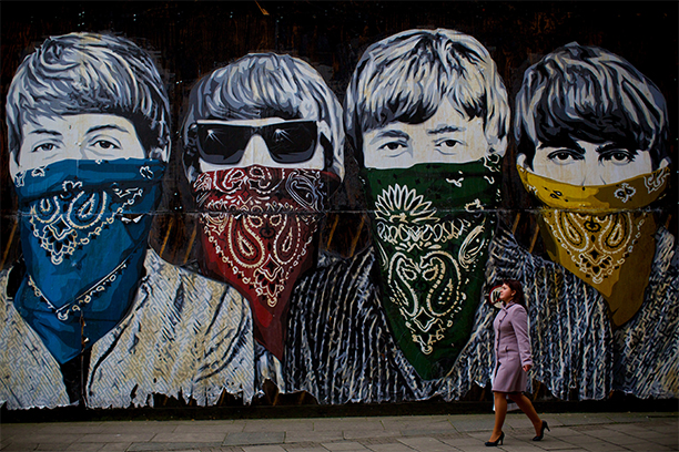 A woman walks past a mural depicting the Beatles wearing bandanas in Central London by Paris-born, Los Angeles?based filmmaker and street artist Thierry Guetta, aka Mr Brainwash on November 8, 2012.  AFP PHOTO / ANDREW COWIE        (Photo credit should read ANDREW COWIE/AFP/Getty Images)