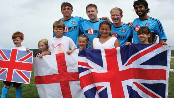 British Soccer coaches hold up Union Jacks with their pupils. (Anderson Parks)