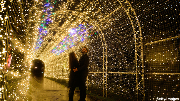 "Miranda Jenatka (L) and Alex Little pose for photographs during the launch event of the ""Christmas at Kew"" lights in Kew Gardens in southwest London on November 25, 2014.  AFP PHOTO / LEON NEAL        (Photo credit should read LEON NEAL/AFP/Getty Images)"