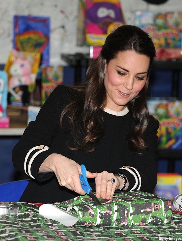 The Duchess lends a hand with the present wrapping inside. (Mark Stewart-Pool/Getty Images)